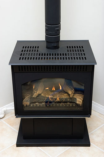 black metal fireplace with stovepipe (fueled by natural gas)