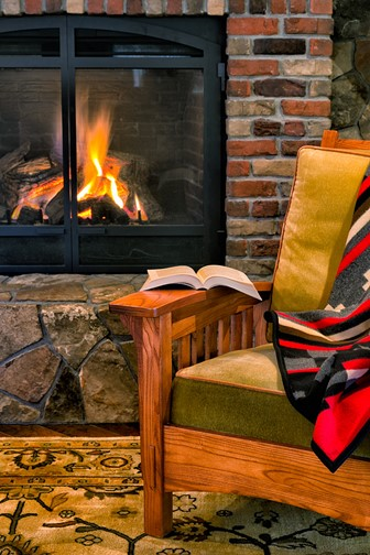 chair and book beside a cozy, rustic fireplace