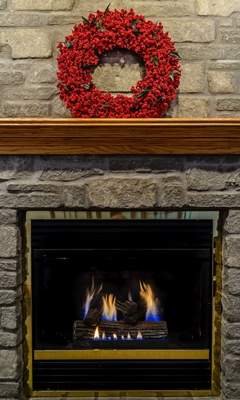 red wreath on the mantle of a stone fireplace